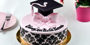 pink and black graduation cake with graduation cap on top